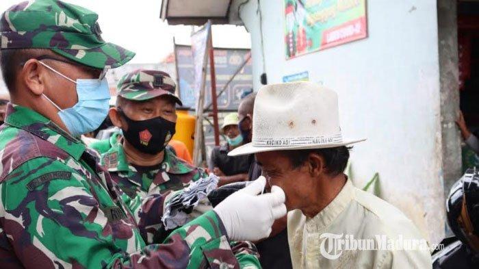 Kasi Ops Korem 084 Bhaskara Jaya Bagikan Masker dan Penyemprotan Disinfektan di Dua Pasar Pamekasan