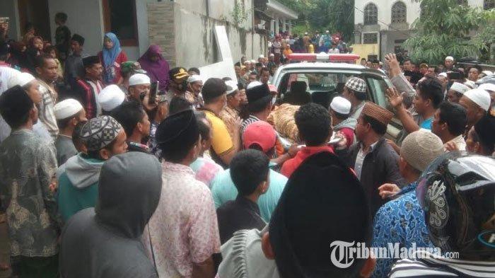 Warga berkerumun melihat tiga santri yang berhasil dievakuasi oleh personel gabungan di lokasi tebing longsor Dusun Jepun, Desa Bindang, Kecamatan Pasean, Kabupaten Pamekasan, Madura, Rabu (24/2/2021).