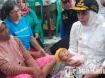 gubernur-jatim-khofifah-menggendong-bayi-korban-banjir-madiun.jpg
