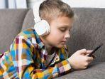ilustrasi-anak-menggunakan-headset-atau-headphone-di-depan-ponsel.jpg