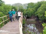 kepala-dlh-bangkalan-anang-yulianto-kanan-menyusuri-jembatan-kawasan-konservasi-mangrove.jpg