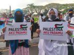 massa-menunjukan-poster-dukungan-untuk-palestina.jpg