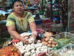 ny-saleho-di-pasar-ki-lemah-duwur-bangkalan-menunjukkan-bawang-putih-yang-dijualnya.jpg