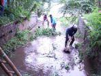 pekerja-membersihkan-sampah-yang-ada-di-saluran-drainase.jpg