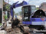 pekerja-menggunakan-alat-berat-sedang-menyelesaikan-pembangunan-saluran-air-di-kota-blitar.jpg