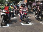 pengendara-sepeda-motor-yang-berhenti-di-lampu-traffic-light-menempati-tanda-untuk-menjaga-jarak.jpg