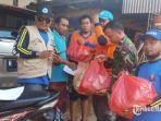personel-bpbd-pamekasan-saat-membagikan-nasi-bungkus-ke-warga-korban-banjir-pamekasan.jpg