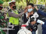petugas-gabungan-saat-bersama-mahasiswi-iain-madura-memakaikan-masker-ke-pengendara.jpg