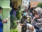 petugas-saat-membagikan-masker-kain-secara-gratis-kepada-warga-surabaya.jpg