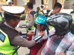 polisi-memakaikan-helm-gratis.jpg