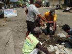 relawan-memasang-paving-di-lubang-jalan.jpg
