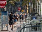turis-masih-berjalan-di-sepanjang-jalan-menuju-pantai-di-miami-beach.jpg