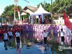 warga-sumenep-menggelar-upacara-pengibaran-bendera-merah-putih-di-atas-sungai.jpg