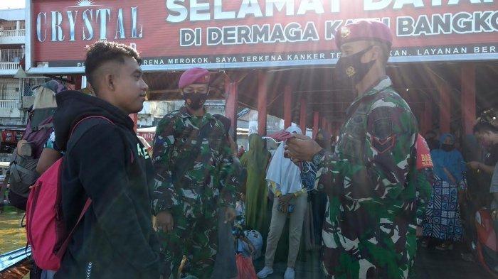 FOTO: Marinir Bagikan Masker ke Wisatawan yang Ingin Liburan di Dermaga Kayu Bangkoa