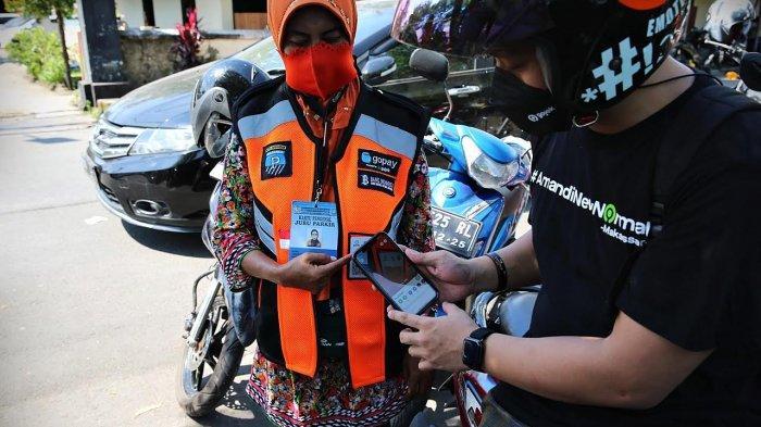 Vice President Strategic Regional Gojek Indonesia Anandita Danaatmadja (kanan), Direktur Utama PD Parkir H Irham Syah Gaffar SE (kedua kiri) dan Deputi Direktur Kantor Perwakilan BI Provinsi Sulsel Bapak Muh. Ali Afthan (kiri) mencoba melakukan pembayaran parkir dengan melakukan scanning barcode QRIS yang tertera di jaket Juru Parkir dengan menggunakan GoPay usai peresmian pembayaran parkir digital menggunakan GoPay melalui Quick Response Code Indonesian Standard (QRIS) di kantor PD Parkir Makassar Raya Jl Hati Mulia Makassar Kamis (22/04/2021). tribun timur/muhammad abdiwan