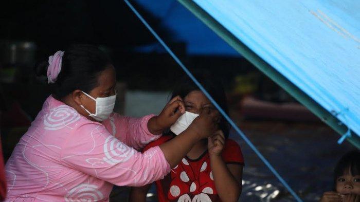 Briptu Muh Anugrah membagikan masker kepada pengungsi yang berada di luar kompleks Stadion Manakarra, Kabupaten Mamuju, Sulbar, Senin (25/1/2021) sore. Ratusan masker dibagi oleh Ba Regident Polda Sulbar ini dengan melihat sulitnya menerapkan protokol kesehatan di pengungsian. Fasilitas pendukung pencegahan penularan juga tidak terlihat. Berdasarkan pantauan di lokasi pengungsian, banyak penyintas lalu lalang tanpa masker.  Mereka juga berkumpul di sekitar tenda, baik dengan anggota keluarga setenda maupun penyintas dari tenda lain, tanpa bermasker. Di sekitar pengungsian juga tidak terlihat fasilitas pencegahan penularan Covid-19, seperti tempat cuci tangan. TRIBUN TIMUR/SANOVRA JR