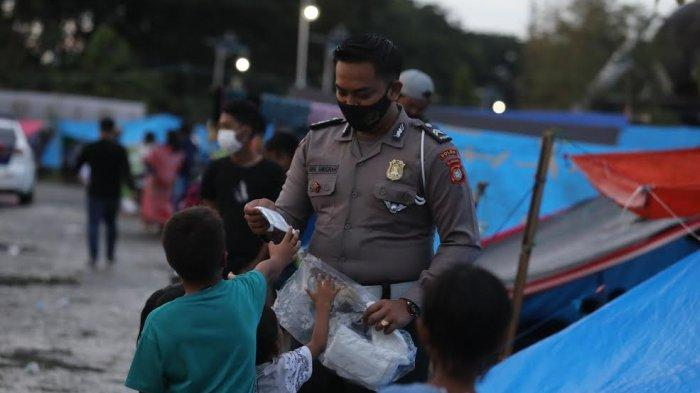 FOTO: Cegah Penularan Covid, Briptu Muh Anugrah Bagi Masker ke Tenda Pengungsi Gempa Sulbar