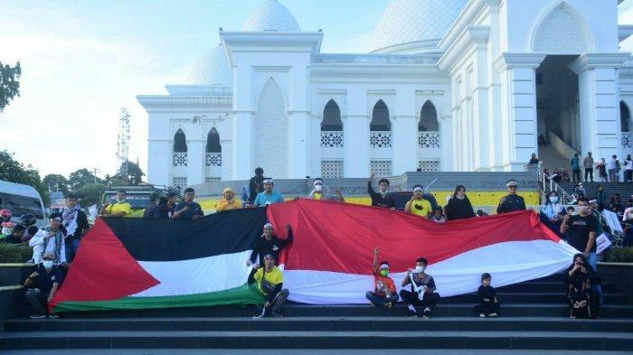 Aliansi Pemuda dan Masyarakat Soppeng Peduli Palestina membentangkan Bendera Merah Putih dan Bendera Palestina di halaman Masjid Raya Soppeng di sela aksi solidaritas kemanusiaan bela Palestina di Soppeng, Sabtu (22/5/2021).