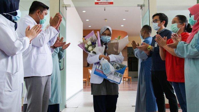 Dokter Rizki Amanda Sari disambut tim medis saat keluar dari Rumah Sakit Badan Pengusahaan Batam, Jumat (1/5/2020). Ia dan drg Fitri dinyatakan sembuh dari Covid-19 setelah sebelumnya menjalani perawatan selama 16 hari di rumah sakit tersebut.