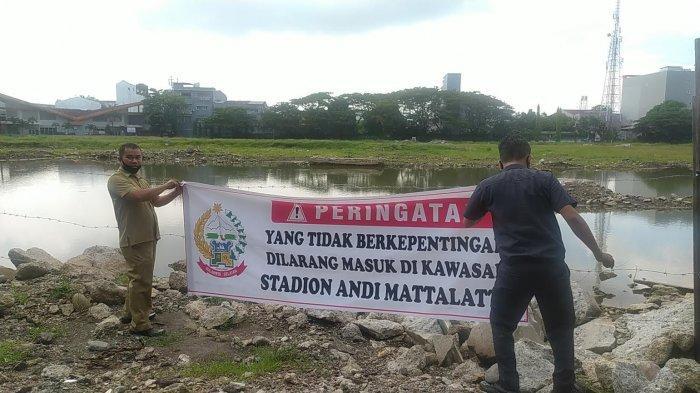 Pemasangan spanduk larangan masuk di kawasan Stadion Mattoanging Makassar, Senin (2452021).