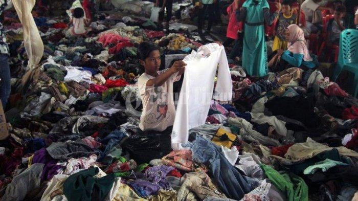 Sejumlah pengungsi korban gempa dan Tsunami Palu memilih baju bekas di gudang Makodam Hasanuddin, Makassar, Selasa (17/10). Bantuan tersebut datang dari perusahaan es krim Aice dengan menggunakan tiga mobil box untuk mengangkut bantuan berupa bahan makanan dan baju layak pakai yang diperlukan pengungsi.