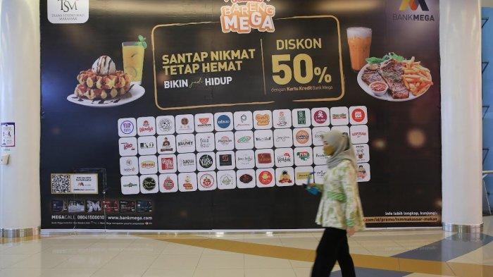 Pengunjung melintas di depan poster Makan Bareng Mega di Trans Studio Mall Makassar, Jumat (1092021). Masih ada waktu untuk menikmati diskon makan 50% di berbagai tenant Food & Beverage favorite hingga 31 Desember 2021.
