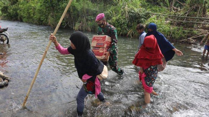 Sejumlah anak-anak melintasi sungai sambil membawa sembako di perbatasan Desa Ulumanda dan Desa Pompenga, Kecamatan Ulumanda, Kabupaten Majene, Sulbar, Jumat (22/1/2021).
