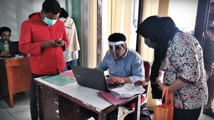 Sejumlah warga antri melakukan input data pendaftaran Penerimaan Peserta Didik Baru (PPDB) jalur zonasi via daring di kantor Dinas Pendidikan Makassar, Selasa (14/7/2020) lalu.