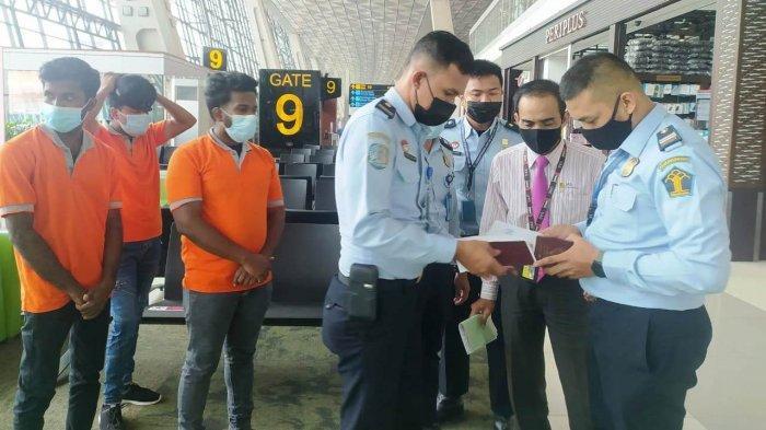 Tiga pria Warga Negara Srilangka melalui proses pengecekan paspor di Bandara Internasional Soekarno sHatta, Jumat (21/5/2021). Mereka dideportasi karena menyalahi aturan sebagai asylum seeker.