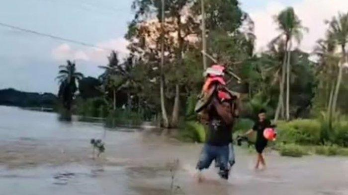 Warga pikul motor saat banjir di Kecamatan Sibulue, Kabupaten Bone, Jumat (14/5/2021).