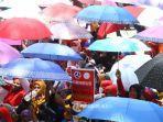 buruh-mengenakan-payung-melakukan-unjuk-rasa-menutup-ruas-jalan.jpg