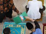 pengurus-masjid-menawarkan-kotak-amal-kepada-jemaah-saat-salat-iduladha-1441-hijriah-1.jpg