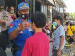 petugas-kepolisian-memakaikan-masker-kepada-seorang-remaja-saat-operasi-yustisi-1.jpg
