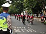 petugas-kepolisian-menjaga-arus-lalu-lintas-yang-dilintasi-pengguna-sepeda-balap-1.jpg