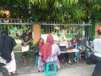 wali-murid-sedang-mengakses-website-ppdb-di-depan-gerbang-smp-negeri-8-makassar.jpg