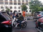 wanita-berkostum-orange-menghalau-pengunjuk-rasa-yang-hendak-menutup-jl-sultan-alauddin.jpg