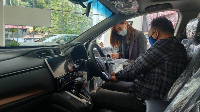 Seorang sales menjelaskan ke kostumer, dalam acara Special Showroom Event 'Soft Launching New Honda CRV Prestige 21'. Di Dealer Honda Martadinata 2 jalan Yos Sudarso Paal 2 Atas, Kota Manado Provinsi Sulut Sabtu (27/2/2021).