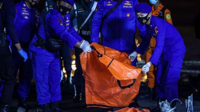 Anggota kepolisian mengangkat kantong jenazah berisi objek temuan dari lokasi jatuhnya pesawat Sriwijaya Air SJ 182 rute Jakarta-Pontianak pada hari ketujuh Operasi SAR pesawat tersebut di Dermaga JICT 2, Tanjung Priok, Jakarta Utara, Jumat (15/1/2021).