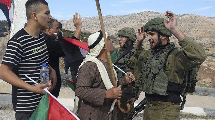 Suasana saat demonstran Palestina berdebat dengan tentara Israel selama protes terhadap pemukiman Yahudi di Lembah Jordania, Tepi Barat, Selasa (24/11/2020).