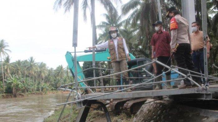 Bupati Bolmong Yasti Soepredjo Mokoagow turun langsung melihat jembatan yang putus karena banjir.