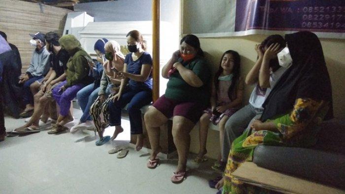Istri korban mengenakan kaos berwarna hijau celana pendek ungu nampak sedang menangis bersama anak perempuannya yang masih berumur 8 tahun.