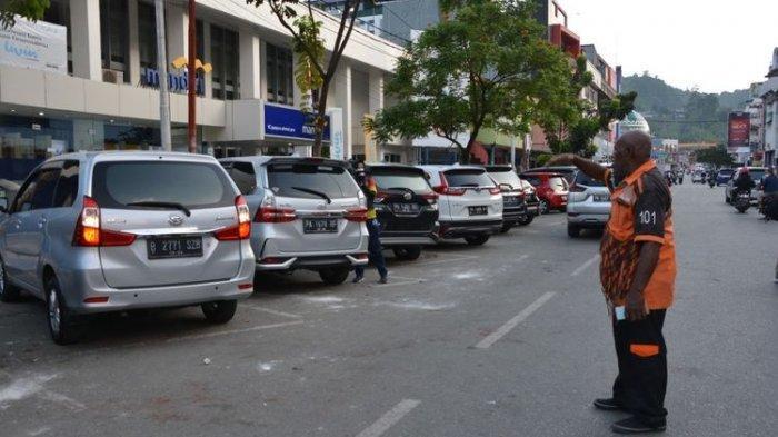 Alex Tiris (baju oranye) tengah menjalani profesinya sebagai juru parkir di pusat Kota Jayapura. Berkat kegigihan dan keikhlasannya dalam bekerja, putra ketiganya, Always Giving Hamonangan Tiris berhasil meraih penghargaan Adi Makayasa AAL, Jayapura, Papua, Rabu (23/6/2021)