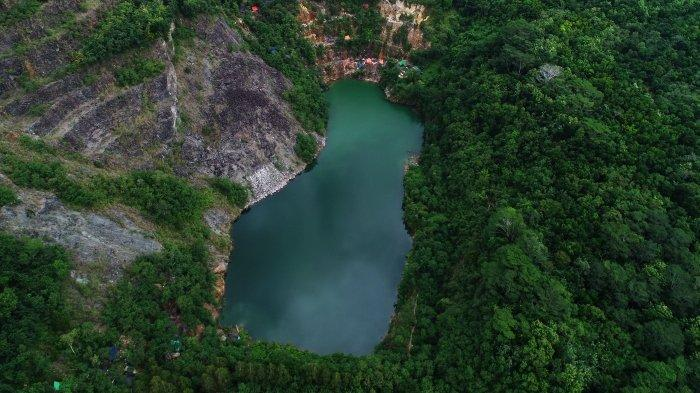 aerial view of a lake surrounded by forest and rock