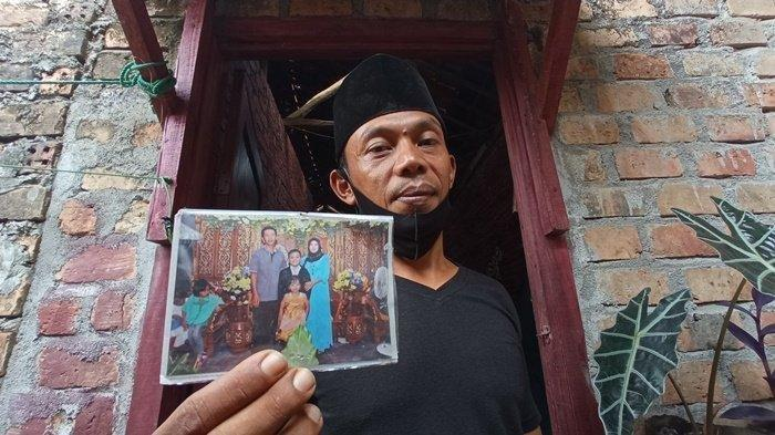 Sukma Fajar (41) adik kandung korban saat menunjukan photo kekuarga almarhum Dedi Sutomo. saat ditemui di kediamannya di OKU Timur, Jumat (30/4/2021)