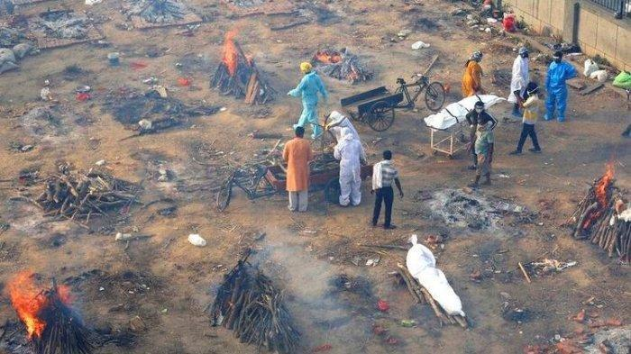 Beberapa tumpukan kayu pemakaman pasien yang meninggal karena penyakit COVID-19 terlihat terbakar di tanah yang telah diubah menjadi krematorium kremasi massal korban virus corona, di New Delhi, India, Rabu (21/4/2021).
