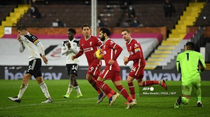 Gelandang Liverpool Mesir Mohamed Salah (tengah) merayakan dengan gelandang Liverpool Inggris Jordan Henderson (kedua dari kanan) dan gelandang Liverpool asal Brazil Roberto Firmino (ketiga dari kiri) setelah mencetak gol pertama mereka dari titik penalti selama pertandingan sepak bola Liga Premier Inggris antara Fulham dan Liverpool di Craven Cottage di London pada 13 Desember 2020.