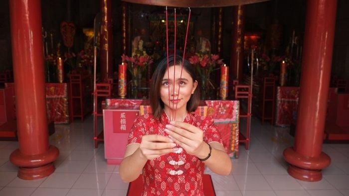 Melisa (24) yang datang bersembahyang dalam rangka menyambut hari raya Imlek di Klenteng Kwan Kong Kota Manado.