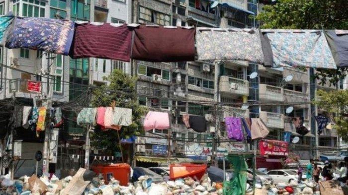 Perempuan menggantungkan sarung mereka di tali jemuran.