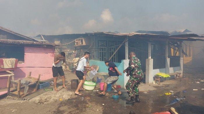 Aksi warga memadamkan api menggunakan es batu dan air dari sumur sebuah sumur yang ada di sekitar rumah warga yang terbakar