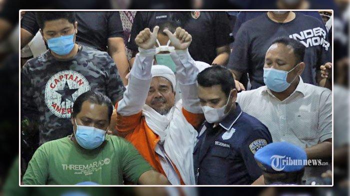 Pemimpin Front Pembela Islam (FPI), Muhammad Rizieq Shihab dengan mengenakan baju tahanan dibawa menuju Rutan Polda Metro Jaya usai menjalani pemeriksaan di Mapolda Metro Jaya, Jakarta Selatan, Minggu (13/12/2020) dini hari. Rizieq Shihab resmi menjadi tersangka dalam kasus pelanggaran protokol kesehatan terkait kerumunan yang terjadi di Petamburan, Tanah Abang, Jakarta Pusat, usai menjalani pemeriksaan selama 15 jam. Tribunnews/Jeprima